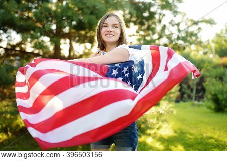 Cute Girl Holding American Flag Outdoors On Beautiful Summer Day. Independence Day Concept. Child Ce
