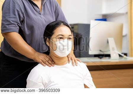 Quarantine asian woman do massage at home with face mask while city lockdown for social distance due to coronavirus pandemic. Massage is one of service business that shutdown while city lockdown.