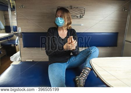 Young Caucasian Woman In Medical Mask Travelling In A Train, Sitting Next To A Window. Woman Protect