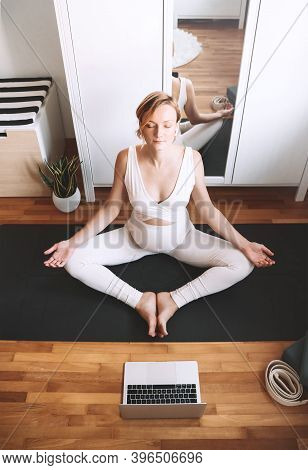 Pregnant Woman Practicing Yoga Online At Home With Laptop.