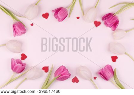Frame made of colourful tulips and red hearts Valentines day background