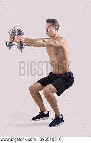 Strength Workout Concept. Powerful Young Sportsman With Dumbbells Doing Squats On Light Studio Backg
