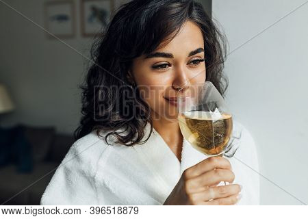 Beautiful Female Enjoying Bocal Of Wine. Young Woman Relaxing At Home.