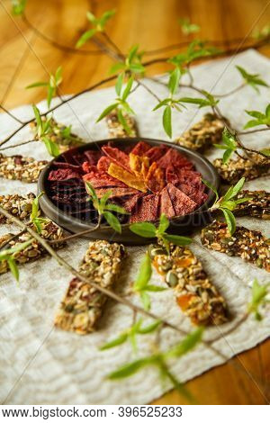 A Circular Composition On The Table With Homemade Fruit Leather Pieces In The Bowl And Granola Bars