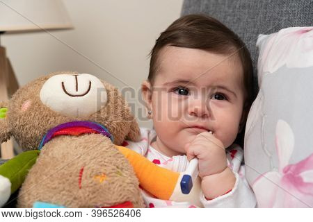 Sick Baby Girl With Thermometer In Mouth For Measuring Body Temperature Holding Colourful Teddy Bear