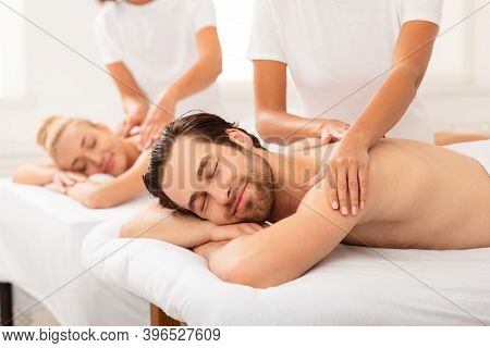 Husband Relaxing During Couples Massage With Wife Enjoying Relaxing Body Treatment While Masseurs Ma