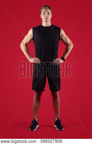 Full Length Portrait Of Determined Male Fitness Model Looking At Camera On Red Studio Background. Se