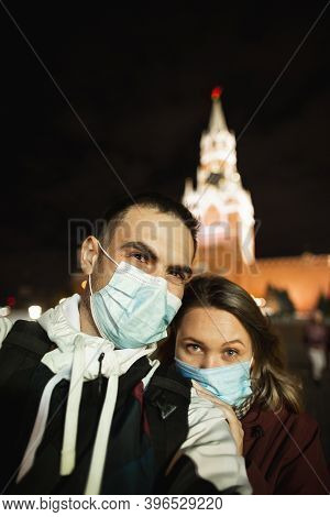Happy Romantic Couple Of Tourists In Medical Masks Makes Selfie Self-portrait In Front Of Kremlin On