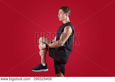 Flexible Millennial Man Stretching His Leg Over Red Studio Background, Side View. Athletic Young Guy