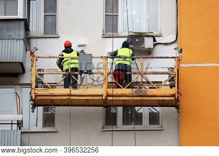 Workers Paints The Wall Of A Panel House. Construction And Repair Works, Residential Building Facade