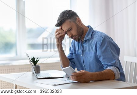 Worried Male Freelancer Looking At Smartphone Screen While Working At Home Office, Received Bad News
