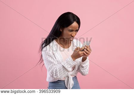 Angry Black Woman Looking At Her Smartphone With Disgust, Reading Annoying Message Or News On Pink S