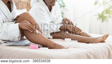 Cropped Of African American Women In Bathrobes Sitting On Bed At Home, Applying Body Lotion On Their