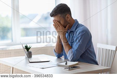 Remote Work Stress. Tired Freelancer Man Sitting At Desk With Laptop At Home Office, Overworked Man