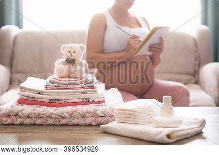 Pregnant Woman Is Getting Ready For The Maternity Hospital, Packing Baby Stuff. Pregnant Woman Prepa