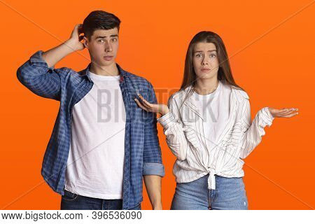 Puzzled Young Couple Do Not Understand What Happening Or Does Something Wrong. Surprised Man Scratch