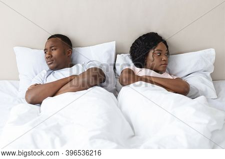 Young Married African American Couple After Fight In Bedroom, Sad Man And Woman Laying In Bed Apar.