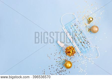 Medical Mask And Antiseptic, Christmas Decorations On Blue Background With Stars Confetti. Medical P