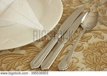 Table Setting With Plate, Knives, Spoon And Napkin. Place Setting Of Dining Set Of An Empty Plate Wi
