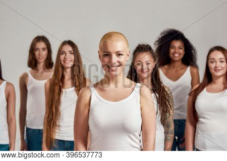 Portrait Of Beautiful Young Caucasian Woman With Shaved Head In White Shirt Smiling At Camera. Group