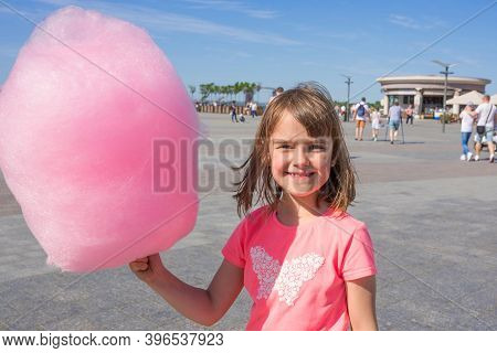 Happy Girl Holding Cotton Candy In An Amusement Park