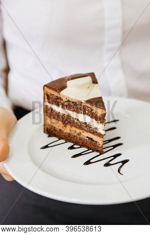 Waitress Holding Plate With Slice Of Chocolate Cake