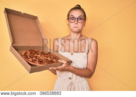 Beautiful caucasian woman holding tasty pepperoni pizza puffing cheeks with funny face. mouth inflated with air, catching air.