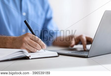 Unrecognizable Man Writing In Notepad And Using Laptop In Office, Taking Notes At Workplace, Using C