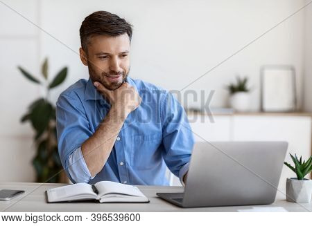 Handsome Male Entrepreneur Using Laptop, Sitting At Desk In Home Office, Looking At Computer Screen