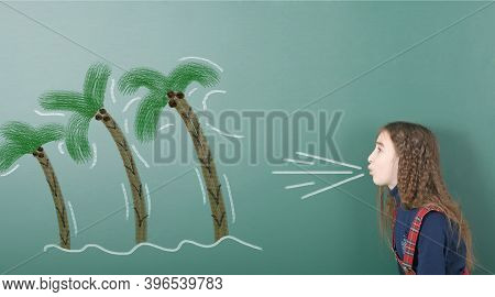 Pre-adolescent Girl Blowing On Painted Palm Tree Which Bend. Portrait Photo On School Board Backgrou