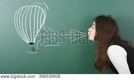 Pre-adolescent Girl Blowing On Painted Balloon Aeronautics. Portrait Photo On School Board Backgroun