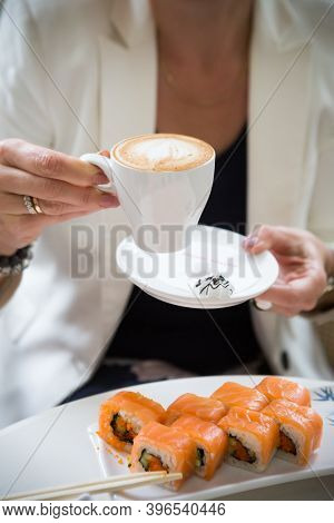 Woman Holding Coffee Cup In Cafe At Lunch