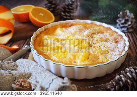 New Year Dessert. Orange Clafoutis With Praline, Powdered Sugar Dressing, Spruce Branch And Pine Con