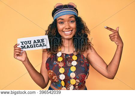 Young african american woman wearing bohemian and hippie style holding you are magical message pointing finger to one self smiling happy and proud