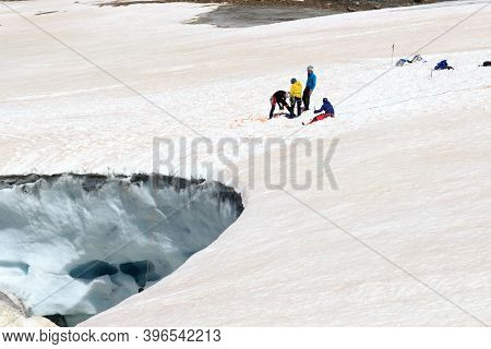 Rope Team Training Crevasse Rescue On Glacier Taschachferner And Mountain Snow Panorama In Tyrol Alp