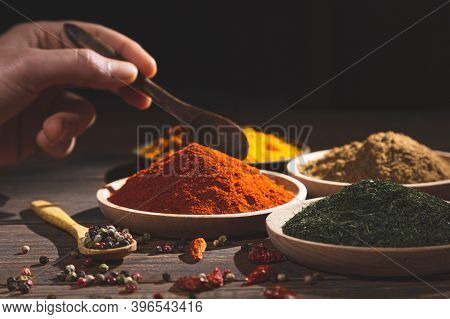 Various Colorful Herbs And Spices On Wooden Table. Hand With A Spoon . Dark Background, Selective Fo