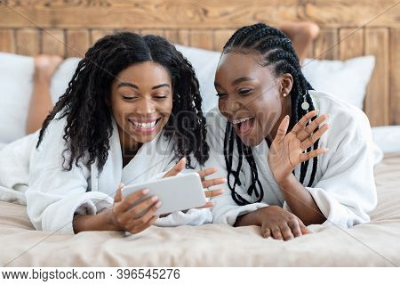 Happy African American Young Women In Bathrobes Laying On Bed And Calling Their Girlfriend, Using Mo