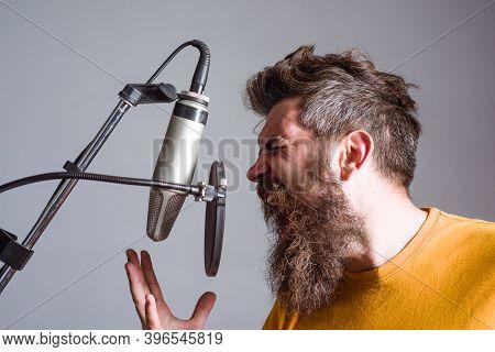 Bearded Man In Karaoke. Man Singing With A Microphone. Singing In Studio. Microphone. Sings A Song.