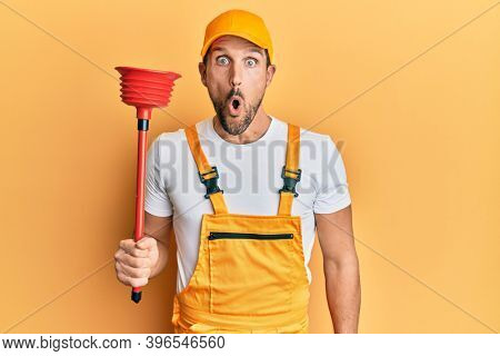 Young handsome man wearing plumber uniform holding toilet plunger scared and amazed with open mouth for surprise, disbelief face
