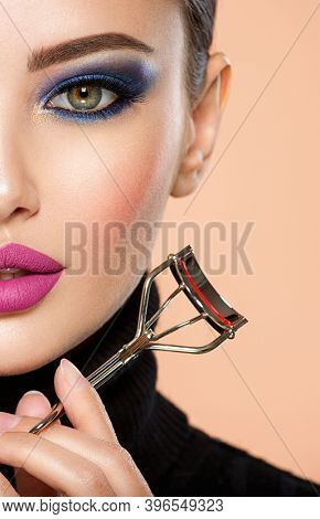 Portrait of a girl with  tools for making makeup near face.  One half face of a beautiful white woman with  bright makeup and the other is natural. Woman holds makeup brush and eyelash curler.