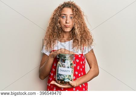 Beautiful caucasian teenager girl holding charity jar with money puffing cheeks with funny face. mouth inflated with air, catching air.