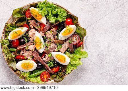 Salad Nicoise With Tuna, Eggs, Green Beans, Tomatoes,  Olives, Lettuce And Anchovies