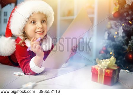 Baby Girl Writes A Letter About Her Magic Dreams To Santa, At Home Near The Christmas Tree.