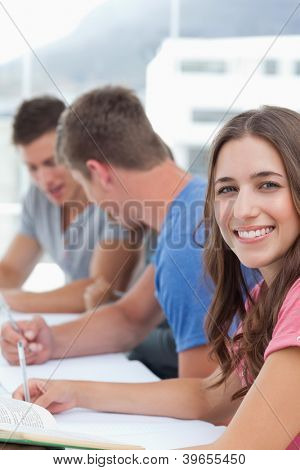 A close up shot of a smiling woman as her friends work in the background