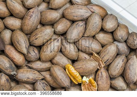 Pecan Nuts Whole With One Nut Shelled In Container - Topview Pecan Nut Background
