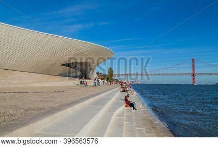 Lisbon, Portugal - October 31, 2020: People near famous MAAT Museum in Lisbon near river Tagus and Landmark 25 of April bridge.