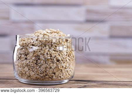 Oatmeal In A Glass Jar On A Wooden Table With Place For Text. Side View. Raw Oatmeal