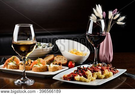 Dinner Concept For Two With Two Glasses Of White Wine, Baked Fish. Dinner Table For Two With Delicio