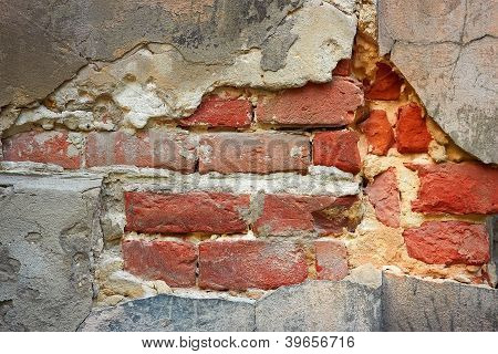 Fragment of old brick wall on a foundation with destroyed stucco close-up poster