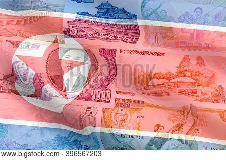 North Korea Won Banknotes On A Waving Flag Background. High Resolution Vintage Photo Of North Korean